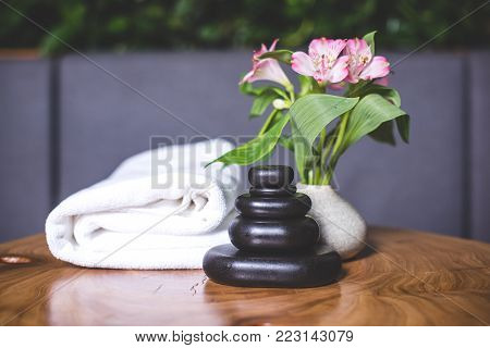 Beautiful view of the towel and massage stones on the table. White-pink daffodils stand in a white vase. Pyramids of stones for massage lie on the wooden table. White towels lie in the background. stock photo