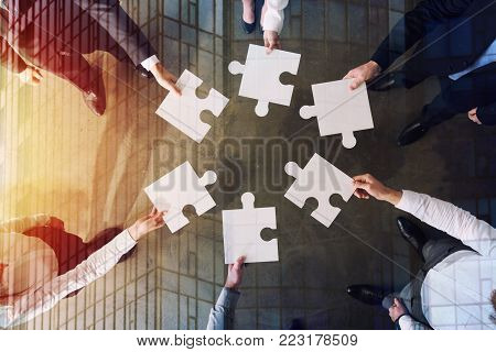 Businessmen working together to build a big puzzle. Concept of teamwork, partnership, integration and startup.
