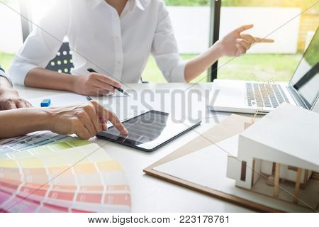 Creative or Interior designers teamwork with pantone swatch and building plans on office desk, architects choosing color samples for design project stock photo