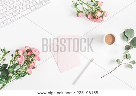 Office desk with computer, rose flowers, eucalyptus branch, pink paper blank. Flat lay, top view, copy space