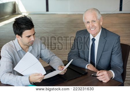 Positive gray-haired senior businessman at meeting with lawyer. Happy successful managing director satisfied work of assistant or advisor. Signing contract concept stock photo