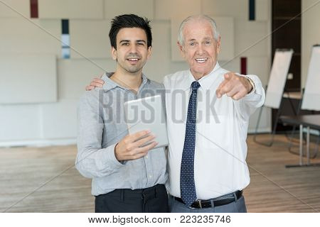 Content senior man in tie pointing at camera and slapping young colleague on shoulder. Mentor and young employee with tablet advertising e-learning course. Business meeting and coaching concept stock photo