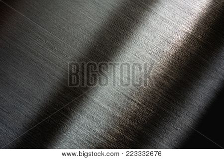 Brushed metal in the dark with slight light reflection. stock photo