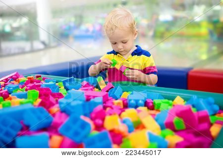 Child playing with colorful construction toy blocks. Educational toys for young kids. Kindergarten or preschool play room. Toddler kid at day care playground. Boy building house with block at daycare stock photo