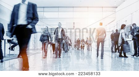 anonymous People standing and walking on a trade show booth, generic background with a blur effect applied