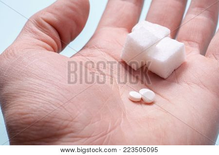 Choice of Sweetener in tablets or regular sugar. Alternative to sugar for diabetics. A man holds sugar and sugar substitute in his hand stock photo