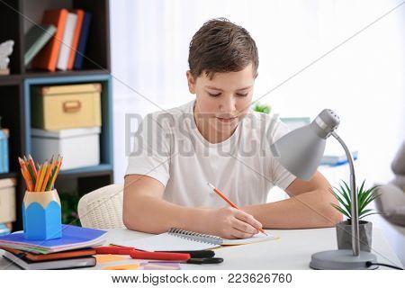 Teenage boy doing homework at table indoors stock photo