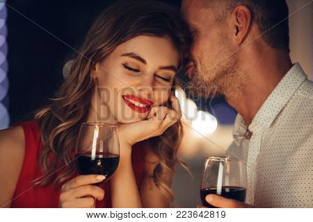 Young handsome man whisper to his gorgeous woman while have romantic dinner and drinking wine on val
