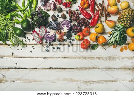 Helathy raw vegan food cooking background. Flat-lay of fresh fruit, vegetables, greens and superfoods over white wooden table, top view, copy space. Clean eating, alkaline diet, vegetarian concept stock photo