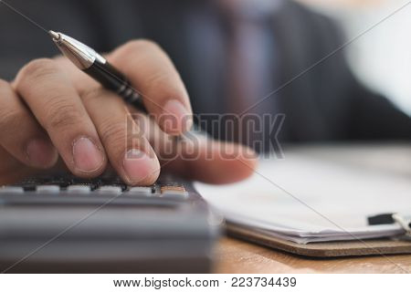 financial adviser working with calculator, business document & computer at office. accountant doing accounting & calculating revenue & budget. bookkeeper making calculation. finance & economy concept stock photo