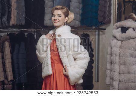 Woman in fur coat, shopaholic. Shopping, seller, fashion model, customer. sensual woman in fur, luxury, moneybags, business. Fashion and beauty, winter, fur. Purchase, shopping, business, moneybags. stock photo