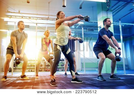 sport, fitness, weightlifting and training concept - group of people with kettlebells exercising in