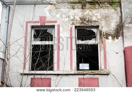 Windows and remains of abandoned damaged and destroyed house by grenade shelling in the war zone stock photo
