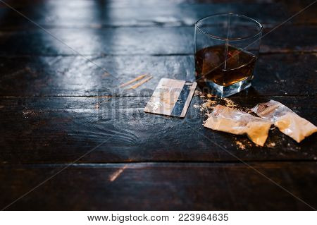 Cocaine and alcohol drink on dark background. Detrimental lifestyle. Bad habits. Alcohol and drug addiction. Important problem of modern society stock photo