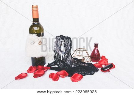 Valentines Day concept. Pink g-strings with wine glasses, roses and candles on white textured background. Isolated. stock photo