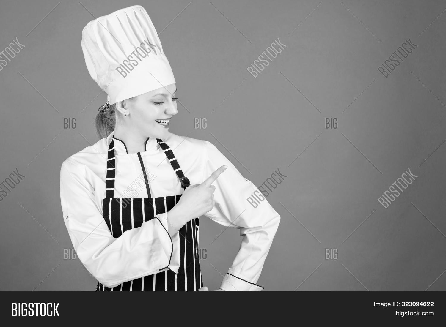 Choose Items From A La Carte Menu. Pretty Female Cook Pointing Finger Away And Offering Menu. Advert