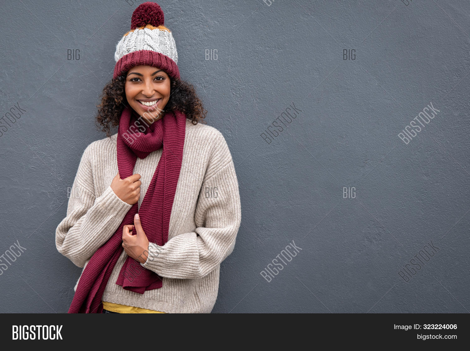 african,african american,african woman,american,attractive woman,background,beautiful,black,cap,casual,cheerful,christmas,cloth,cold,copy space,cozy,expression,fall,fashion,fashionable,girl,gray,gray wall,grey background,happiness,happy,holiday,joy,knitted hat,knitted scarf,looking,looking at camera,portrait,scarf,season,smile,standing,stylish,sweater,wall,warm,warm clothes,warm sweater,winter,winter clothes,winter holiday,woman,woolen,young