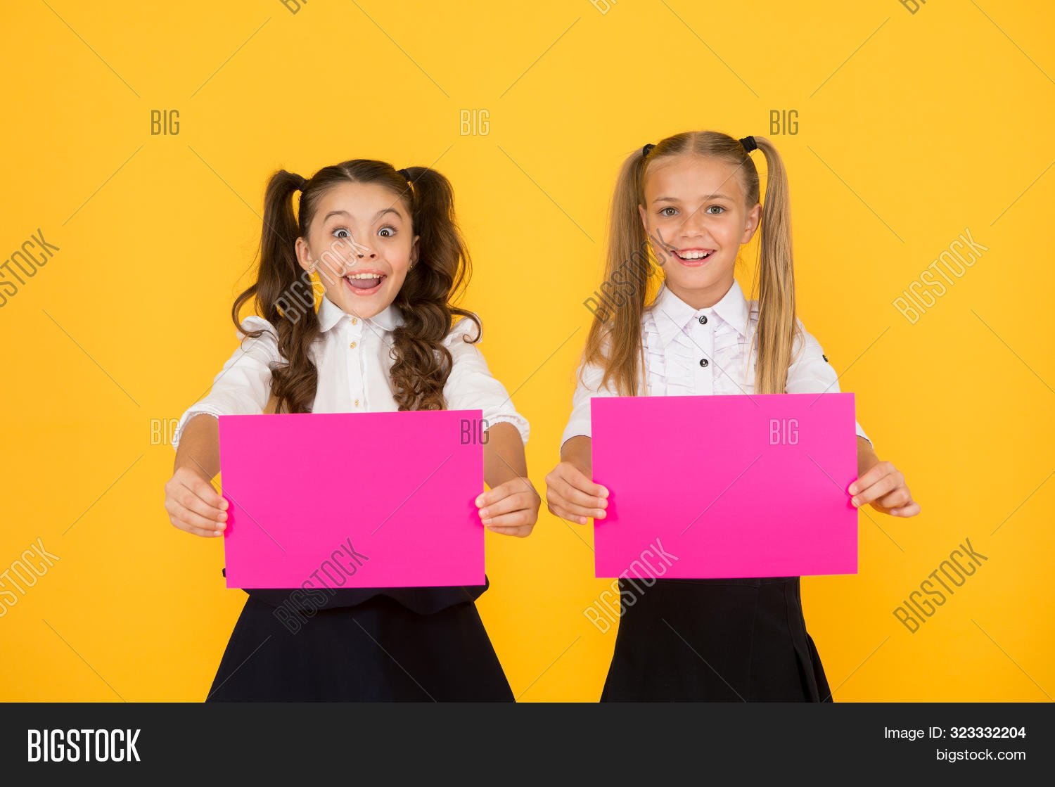 Promote with advertising. Happy small children showing pink paper sheets for advertising on yellow background. Little girl advertising product or event. Advertising and marketing, copy space.