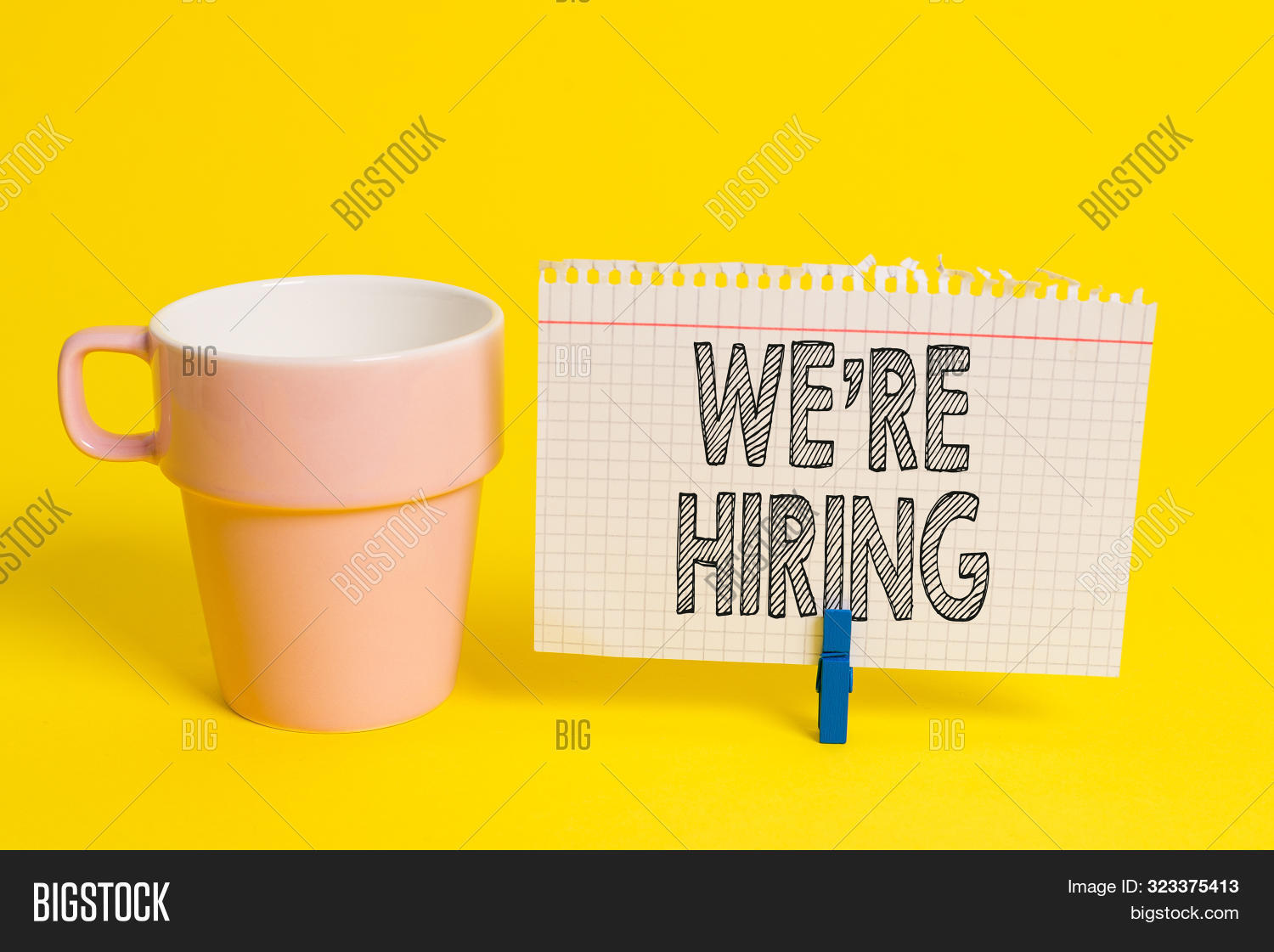 Writing note showing We Re Hiring. Business photo showcasing Advertising Employment Workforce Placement New Job Cup empty paper blue clothespin rectangle shaped reminder yellow office.