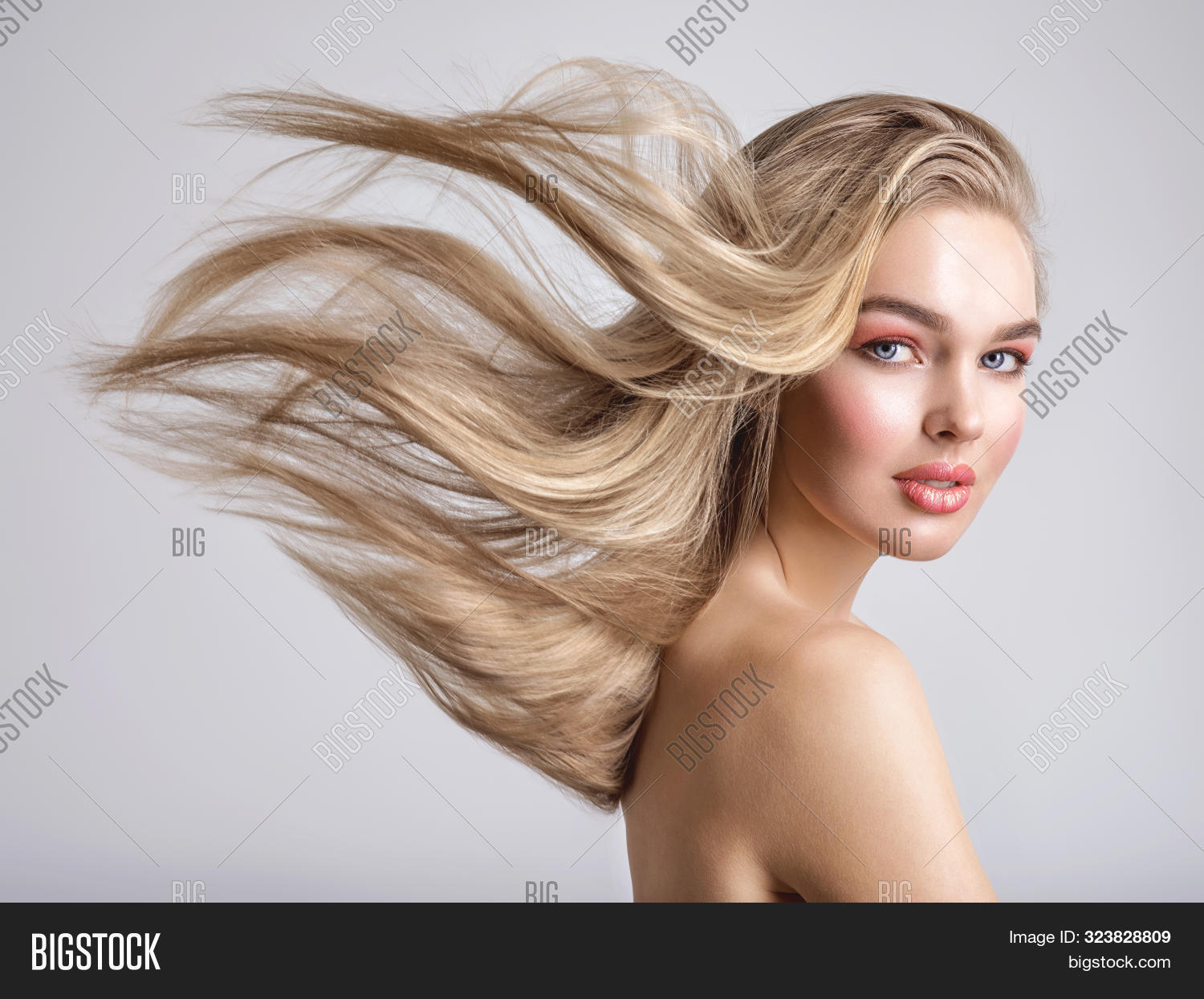 Portrait of a blonde beautiful woman with a long straight light hair. Woman with hair flying in the