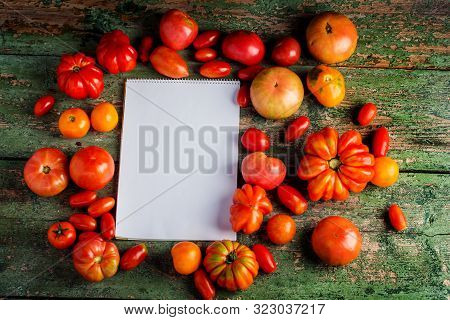Flat-lay of fresh colorful ripe Fall or Summer heirloom tomatoes variety over rustic background with blank paper top view, copy space. Local market seasonal produce. stock photo