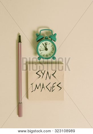 Text sign showing Sync Images. Conceptual photo Making photos identical in all devices Accessible anywhere Metal vintage alarm clock wakeup blank notepad marker colored background. stock photo