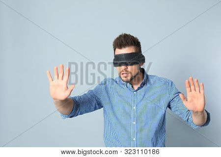 Man with light blue blindfold on white background stock photo