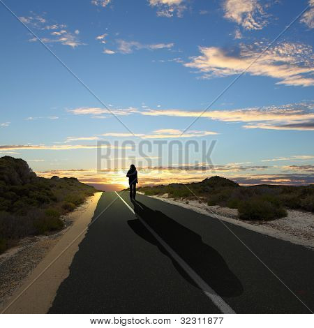 Collage with a human figure walking away along the coubtry road stock photo