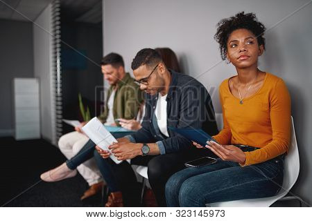 Unemployed young african american woman feeling stressed about tedious waiting sitting in queue with other candidates for job interview stock photo