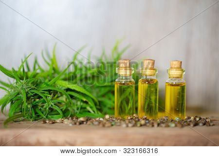 CBD oil hemp products, Medicinal cannabis with extract oil in a bottle on a wooden table. Medical cannabis concept stock photo