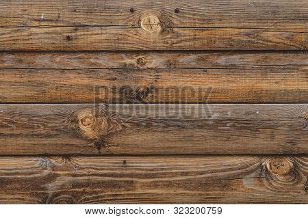 Dark wooden fence. Shabby table, dirty pine lumber. Old wood boards. Pattern, surface of logs. Backgrounds of cracked planks, bar. Brown slats. Parallel bars. stock photo