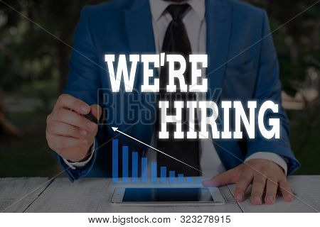 Handwriting text writing We Re Hiring. Concept meaning Advertising Employment Workforce Placement New Job Male human wear formal work suit presenting presentation using smart device. stock photo