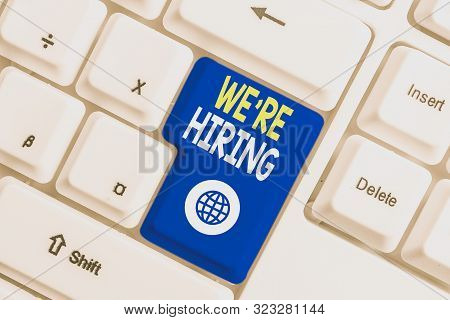 Writing note showing We Re Hiring. Business photo showcasing Advertising Employment Workforce Placement New Job White pc keyboard with note paper above the white background. stock photo