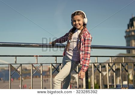 Best music apps that deserve a listen. Make your kid happy with best rated kids headphones available right now. Girl child listen music outdoors with modern headphones. Enjoy music everywhere. stock photo