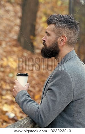 Man bearded hipster prefer coffee take away. Businessman bearded guy drink coffee outdoors. Hipster hold paper coffee cup and enjoy park environment. Relaxing coffee break. Drink it on the go. stock photo