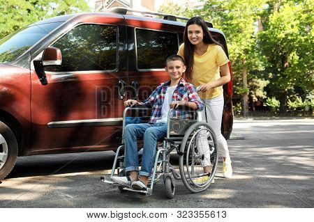 Young woman with boy in wheelchair near van outdoors stock photo