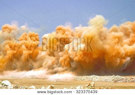 Yellow dust clouds on the construction site in the desert during detonator blasting stock photo