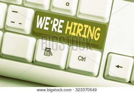 Conceptual hand writing showing We Re Hiring. Business photo text Advertising Employment Workforce Placement New Job White pc keyboard with note paper above the white background. stock photo