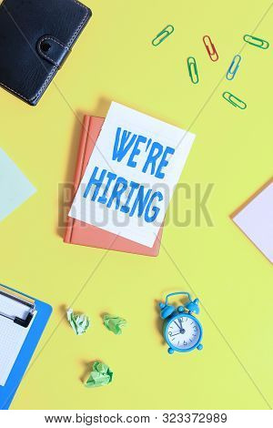 Text sign showing We Re Hiring. Conceptual photo Advertising Employment Workforce Placement New Job Pile of empty papers with copy space on the table. stock photo