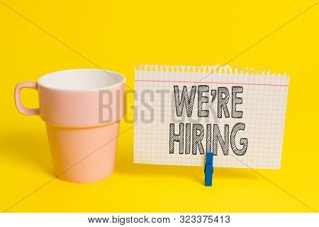 Writing note showing We Re Hiring. Business photo showcasing Advertising Employment Workforce Placement New Job Cup empty paper blue clothespin rectangle shaped reminder yellow office. stock photo
