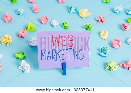 Word writing text Web Marketing. Business concept for Electronic commerce Advertising through internet Online seller Colored crumpled papers empty reminder blue floor background clothespin. stock photo