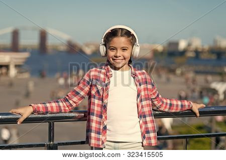 Enjoy music everywhere. Best music apps that deserve a listen. Girl child listen music outdoors with modern headphones. Make your kid happy with best rated kids headphones available right now. stock photo