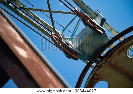 Steel cable and winch. Part of an old winch with a steel rope on a lift. Detail of the cableway. Close-up view of steel big wheel of cableway in mountains against the blue sky stock photo