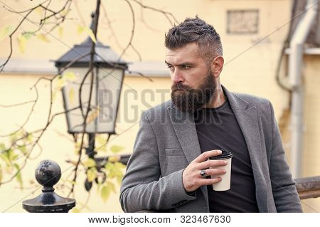 Relaxing coffee break. Hipster hold paper coffee cup and enjoy park environment. Drink it on the go. Man bearded hipster prefer coffee take away. Businessman bearded guy drink coffee outdoors. stock photo
