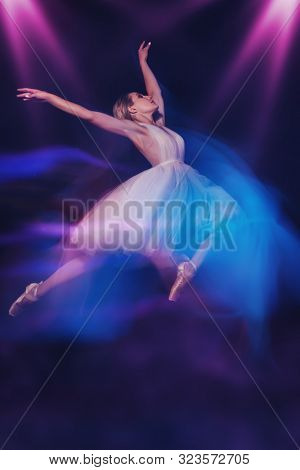 A full length portrait of a refined female ballet dancer posing in the studio over the black background. Talent, fashion for ballet dancers.  stock photo