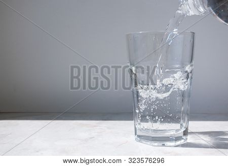 Stream of clean water pouring from a bottle into a glass with a splash. Modern minimal interior background. Hydratation concept stock photo