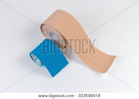 Blue and flesh-colored elastic therapeutic tapes on light surface stock photo