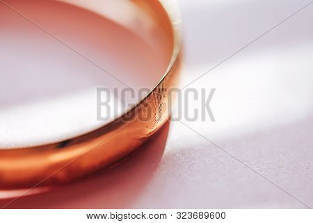 golden bracelet on pink background sun light selected focus macro close up. stock photo