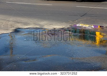 Accident of water supply, sewerage. Water flows from hatch of road sewage system. Dirty sewer flows down fountain along road. Water flows from hatch. Fountain flows down road from sewer stock photo