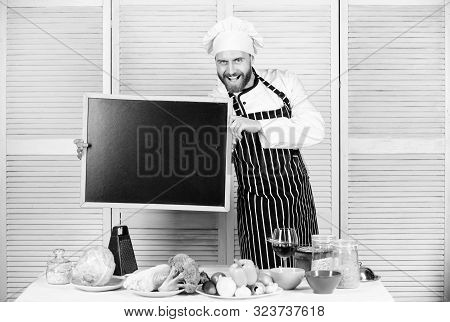 Learning to cook vegetables. Man holding empty blackboard. Chief cook teaching master class in cooking school. Master cook giving cooking class. Education of cooking and food preparation, copy space stock photo